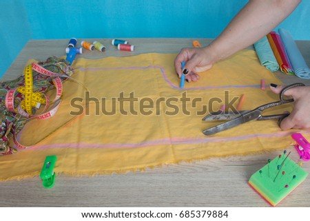 Close up of  woman's hands drawing a pattern on yellow tissue. Measuring tape and sewing accessories. A tailor is laying out a dress/Sewing layout #685379884