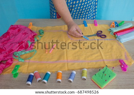 Close up of  woman's hands drawing a pattern on yellow tissue. Measuring tape and sewing accessories. A tailor is laying out a dress/Sewing layout #687498526