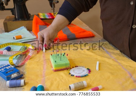 Close up of woman's hands drawing a pattern on yellow tissue. Measuring tape and sewing accessories. A tailor is laying out a dress. Sewing layout, tailoring concept #776855533