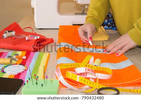 Close up of woman's hands drawing a pattern on yellow tissue. Measuring tape and sewing accessories. A tailor is laying out a dress. Sewing layout, tailoring concept #790432480