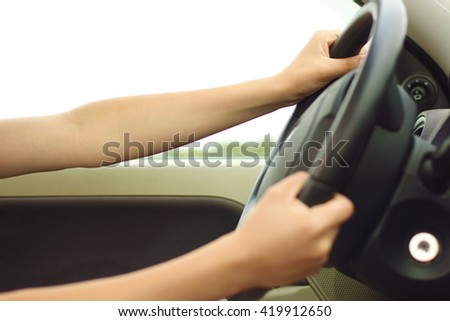 Close up of woman's hands driving a car. Picture of girl's arms holding steering wheel inside auto. Young female sitting indoor on summer outdoor background. no face