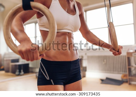 Close up of woman\'s hands holding gymnastic rings. Fit female working out with rings at gym.