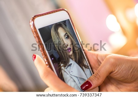 Close up of woman's hands holding smart phone while taking instant selfie photo for social networks.