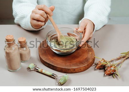 Close up of woman's hands in white shirt mixing organic ubtan with a spoon in wooden bowl. Traditional natural herbal cosmetic agent for skin and hair care handmade creation.