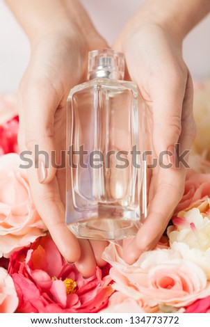 close up of woman\'s hands showing perfume