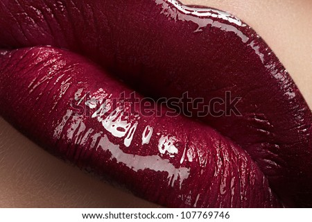 Close-up of woman's lips with bright fashion dark red glossy makeup. Macro lipgloss cherry make-up. Sexy kiss