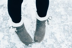 Close up of woman's suede winter boot on white snow