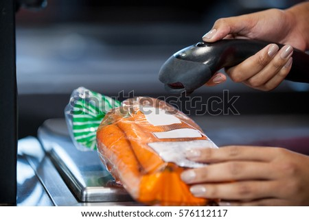 Close-up of woman scanning goods at checkout counter in supermarket