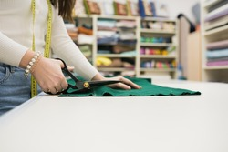 Close up of woman seller cutting fabrics in textile store. Seamstress using scissors to trim the material on work table. Drapery shop. Small Business Concept
