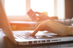 Close Up Of woman Shopping Online Using Laptop With Credit Card