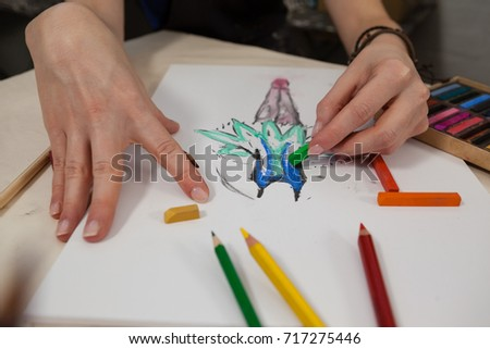 Close-up of woman sketching in drawing book at table