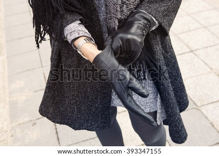 close-up of woman standing in the street putting on her black leather gloves