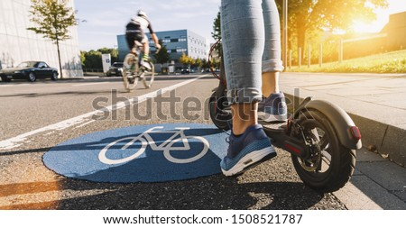 Close up of woman start to riding a electric scooter or kick scooter at cityscape on a Bicycle road sign way