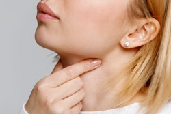 Close up of woman touches fingers of sore throat, isolated on gray background. Thyroid gland, painful swallowing, tonsillitis, laryngeal swelling concept. Inflammation of the upper respiratory tract