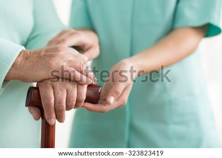 Close-up of woman using cane assisted by physiotherapist ストックフォト ©