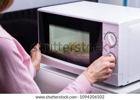 Close-up Of Woman Using Microwave Oven For Heating Food At Home