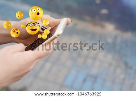 Close-up of woman using smartphone sending emojis. Social concept.