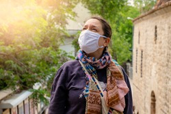 Close up of woman wearing protective face mask, get ready for Coronavirus and pm 2.5 fighting and show stop hands gesture for stop corona virus outdoor beside road in background.