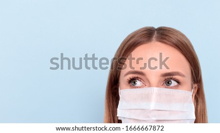 Close up of woman wearing protective mask, looking aside at copy space, isolated on blue background. Flu, allergy, protection against virus, coronavirus pandemic - covid-19. Medical mask advertising