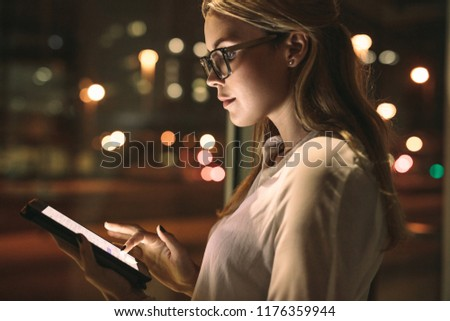 Close up of woman wearing spectacles standing in office using tablet computer. Business woman using a tablet computer at work.