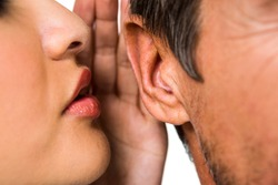 Close-up of woman whispering in man ear