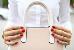 Close-up of woman with beautiful bright red manicure holding trendy bag. Pastel pink colour. Stylish handbag with white handles. Luxury expensive thing. Fashion concept