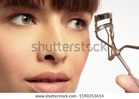 Close-up of woman with eyelash curler