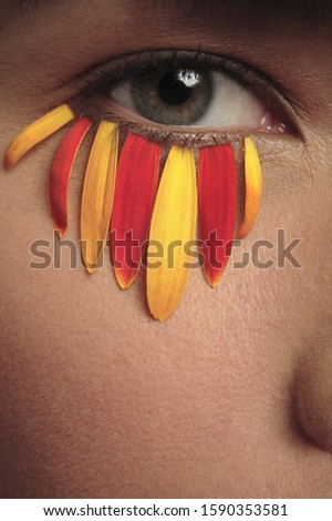 Close-up of woman with flower petals under eye