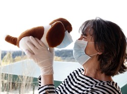 close-up of woman with mask and latex gloves  by the coronavirus lifting a stuffed puppy in her arms, during the covid-19 quarantine