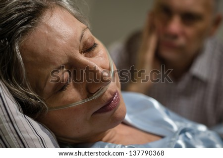 Close up of woman with nasal cannula and worried husband