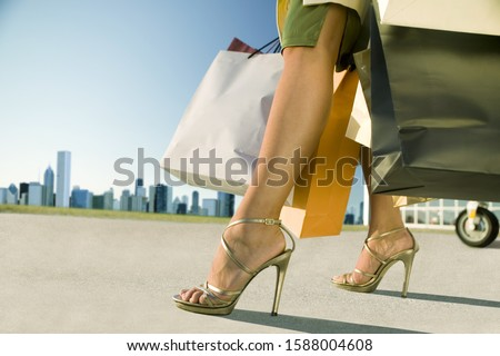 Close up of woman with shopping bags on airport tarmac