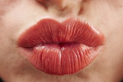 close up of womans pouting lips with red lipstick