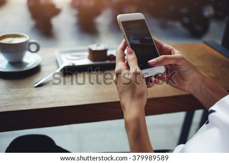 Close up of women's hands holding cell telephone with blank copy space scree for your advertising text message or promotional content, hipster girl watching video on mobile phone during coffee break  #379989589