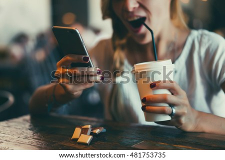 Close up of women\'s hands holding cell telephone with blank copy space scree for your advertising text message or promotional content, hipster girl watching video on mobile phone during coffee break