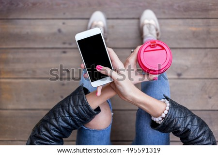 Close up of women\'s hands holding cell telephone with blank copy space screen for your advertising text message or promotional content. Young hipster girl sitting on Wooden floor and using smart phone