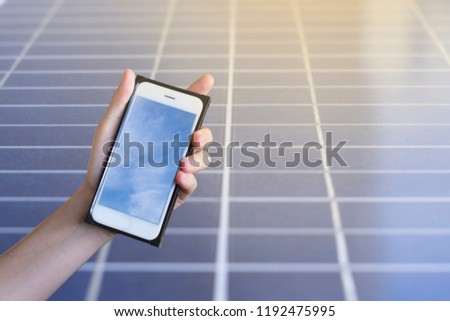 Close up of women's hands holding cell telephone with solar panel on background. Solar energy concept with green energy