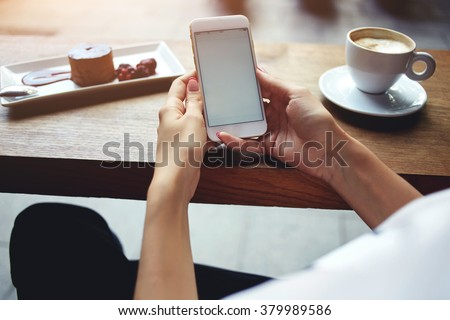 Close up of women's hands holding mobile phone with blank copy space screen for your advertising text message or promotional content, female reading news on cell telephone during rest in coffee shop