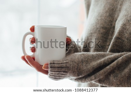 Close up of women's hands holding white mug with blank copy space scree for your advertising text message or promotional content, sweet coffee or tea. #1088412377