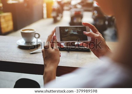 Close up of women\'s hands photographing sweet dessert on mobile phone for social network picture, hipster girl making photo with cell telephone camera of her morning breakfast while sitting in cafe