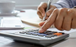 Close-up of women using calculators and note-taking, accounting reports, cost-calculation ideas and saving money.