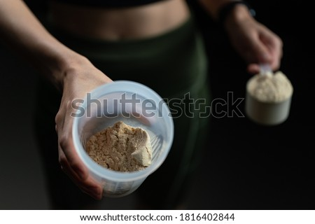 Close up of women with measuring scoop of whey protein, jar and shaker bottle, preparing protein shake.