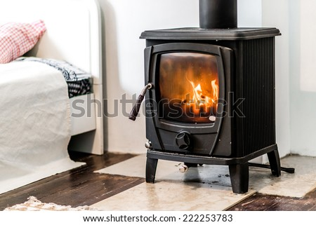 Close up of wood burning stove heating appliance in bedroom flame inside of household equipment. Cozy comfortable for people cold weather easy indoors heating concept Foto d'archivio ©