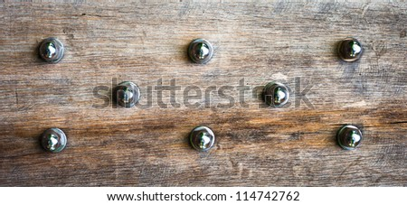 Close up of wood panel studded with bolts