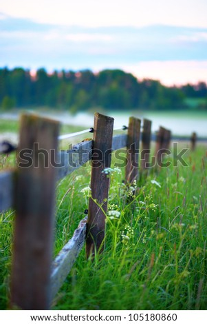 Close up of wooden fence on field on foggy morning