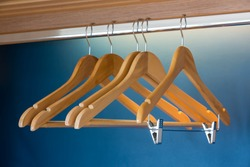 Close up of wooden hangers inside a blue closet with selective focus on the stainless pin.