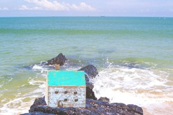 Close up of Wooden house model on the rock with beautiful blue sea with soft wave background, Christian concept from bible, wise man built  house on the rock