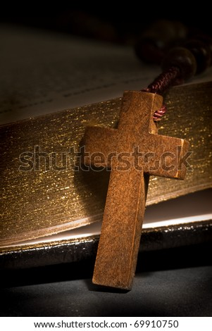 Close up of wooden rosary cross with holy bible