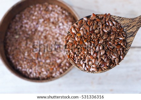 Close up of wooden spoon of flax seeds.
