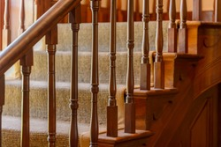 Close up of wooden stair with carved spindles.