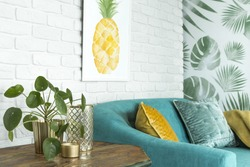 Close-up of wooden table with plant, vase and candle next to blue couch with yellow and green cushions in simple living room